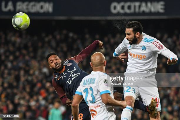 Marseille's French defender Adil Rami heads the ball despite Montpellier's Beninese midfielder Stephane Sessegnon during the French L1 football match...