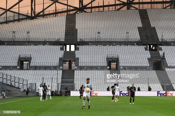 Marseille's French defender Boubacar Kamara runs with the ball in front of empty tribunes as the UEFA Europa League Group H firstleg football match...