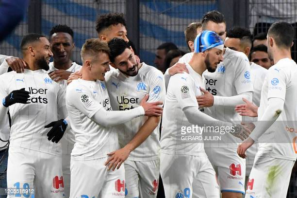 Marseille's French defender Jordan Amavi is congratulated by his teammates after scoring a goal during the French L1 football match between Olympique...