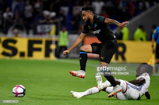 Marseille's French defender Jordan Amavi tries to avoid the tackled by Lyon's Burkinabe forward Bertrand Traore during the French L1 football match...