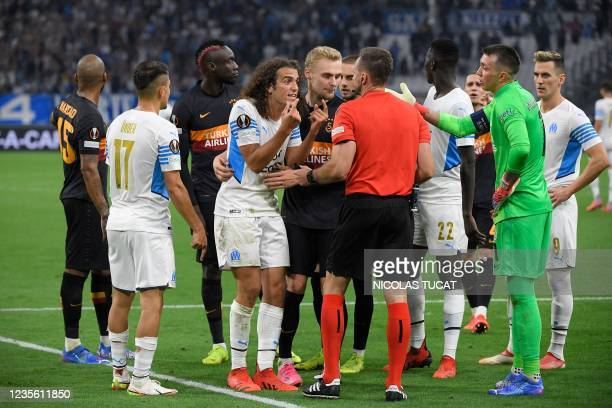 Marseille's French defender Matteo Guendouzi argues with Polish fourth official Bartosz Frankowski after he cancelled a spot-kick call after checking...