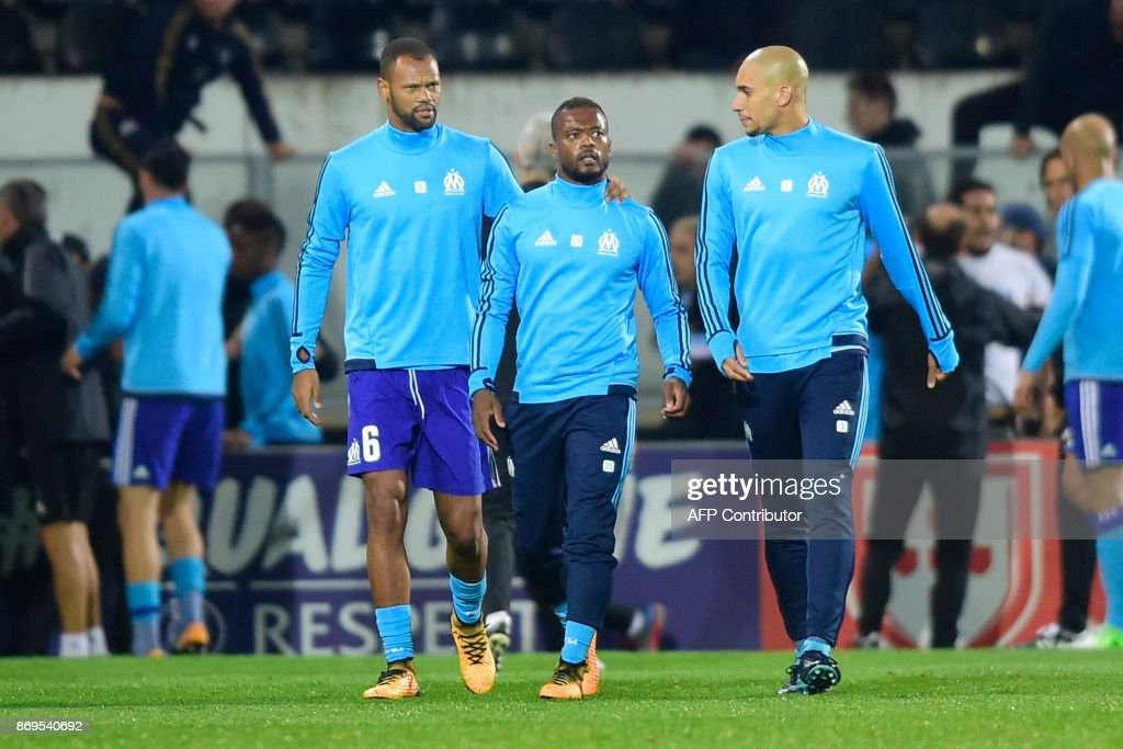 Marseille's French defender Patrice Evra (C) is escorted off the pitch by teammates Portuguese defender Rolando and Brazilian defender Doria after an argument with supporters before the start of the UEFA Europa League group I football match Vitoria SC vs Marseille at the D. Afonso Henriques stadium in Guimaraes on November 2, 2017. /