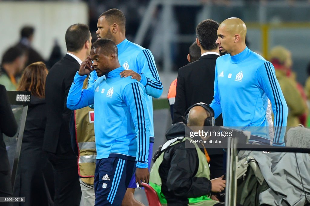 Marseille's French defender Patrice Evra (C) is escorted off the pitch by teammates Portuguese defender Rolando and Brazilian defender Doria (R) after an argument with supporters before the start of the UEFA Europa League group I football match Vitoria SC vs Marseille at the D. Afonso Henriques stadium in Guimaraes on November 2, 2017. /