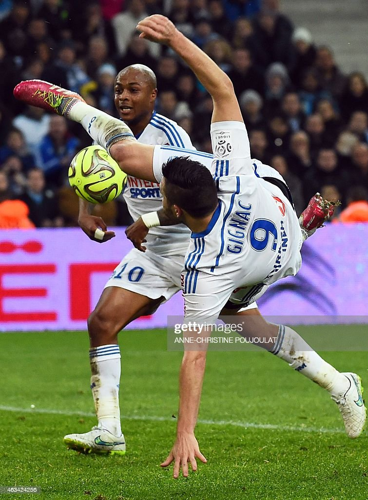 Marseille's French forward Andre-Pierre Gignac (R) jumps for the ball next to Marseille's Ghanaian forward Andre Ayew during the French L1 football match Marseille vs Reims on February 13, 2015 at the Velodrome stadium in Marseille, southern France.