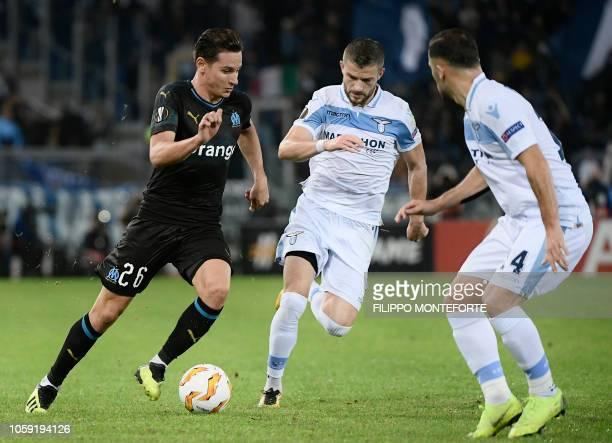 Marseille's French forward Florian Thauvin chammenges Lazio's Kosovo midfielder Valon Berisha and Lazio's Danish defender Riza Durmisi during the...