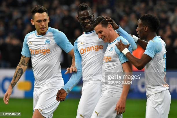 Marseille's French forward Florian Thauvin is congratulated by Marseille's Italian forward Mario Balotelli Marseille's Argentine midfielder Lucas...