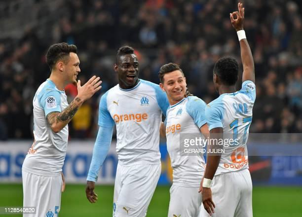 Marseille's French forward Florian Thauvin is congratulated by Marseille's Italian forward Mario Balotelli , Marseille's Argentine midfielder Lucas...