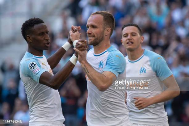 Marseille's French forward Valere Germain jubilates after scoring a goal with Marseille's Guinean midfielder Bouna Sarr and Marseille's French...