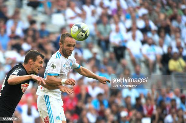 Marseille's French forward Valere Germain heads the ball next to Angers' French defender Romain Thomas during the French L1 football match between...