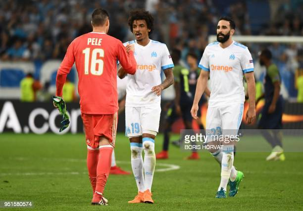 Marseille's French goalkeeper Yohann Pele Brazilian midfielder Luiz Gustavo and French defender Adil Rami celebrate their victory at the end of the...