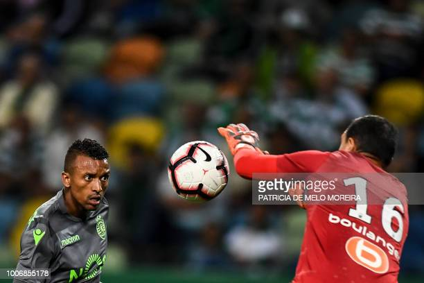 Marseille's French goalkeeper Yohann Pele stops a header by Sporting's Portuguese forward Nani during a friendly football match between Sporting and...