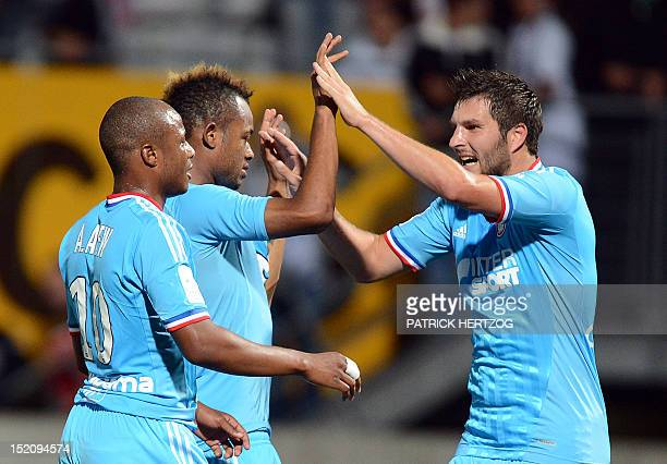 Marseille's French midfielder AndrePierre Gignac celebrates with teammates Marseille's Ghanaian forward Andre Ayew and his brother Jordan Ayew after...