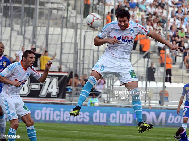 Marseille's French midfielder AndrePierre Gignac heads the ball to score next to Marseille's French midfielder Morgan Amalfitano during their French...