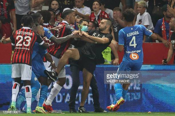 Marseille's French midfielder Dimitri Payet reacts as players from OGC Nice and Olympique de Marseille stop a fan invading the pitch trying to kick...