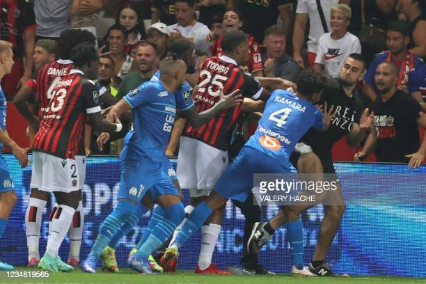 Marseille's French midfielder Dimitri Payet reacts as players from OGC Nice and Olympique de Marseille stop a fan invading the pitch during the...