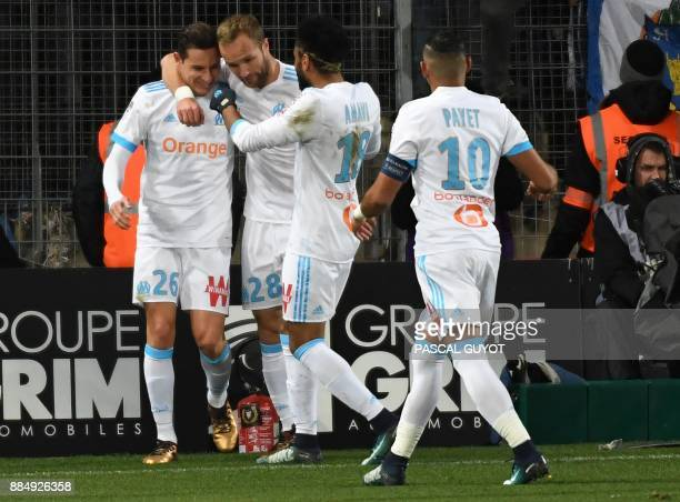 Marseille's French midfielder Florian Thauvin is congratulated by Marseille's French forward Valere Germain Marseille's French defender Jordan Amavi...