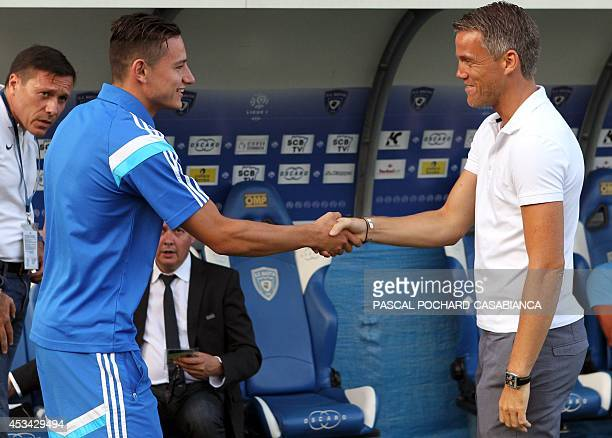 Marseille's French midfielder Florian Thauvin shakes hands with former Bastia's goalkeeper Mickael Landreau before the French L1 football match...