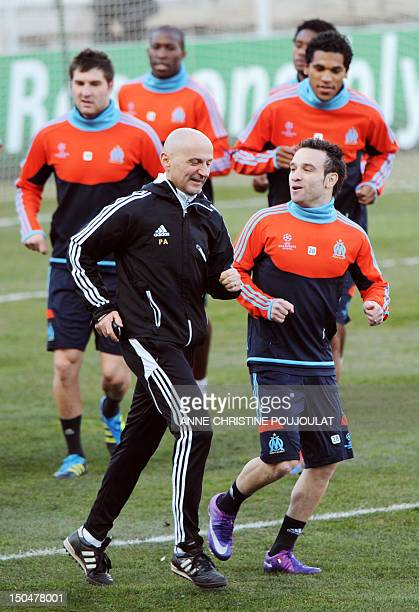 Marseille's French midfielder Mathieu Valbuena runs with assistant coach Italian Antonio Pintus during a training session on February 21 2012 at the...