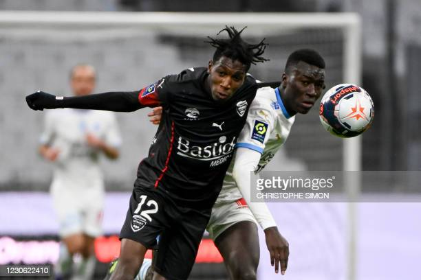 Marseille's French midfielder Pape Gueye vies with Nimes' French midfielder Lamine Fomba during the French L1 football match between Olympique de...