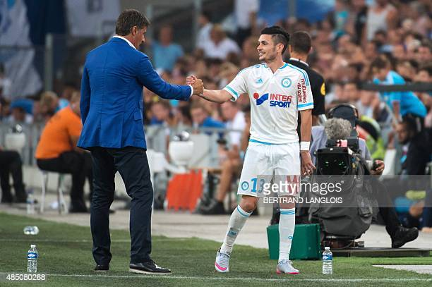Marseille's French midfielder Remy Cabella shakes hands with Marseille's Spanish head coach Jose Miguel Gonzalez Martin del Campo aka Michel during...