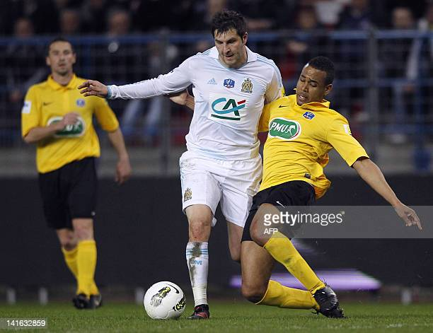 Marseille's French striker AndréPierre Gignac fights for the ball with Quevilly's Alexandre Vardin during the French Cup football match between...