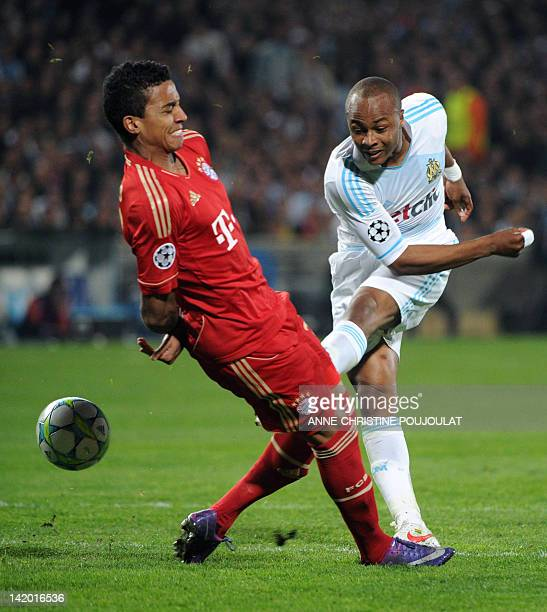 Marseille's Ghanean forward André Ayew kicks the ball in front of Bayern Munich's Brazilian midfielder Luiz Gustavo during the UEFA Champions League...