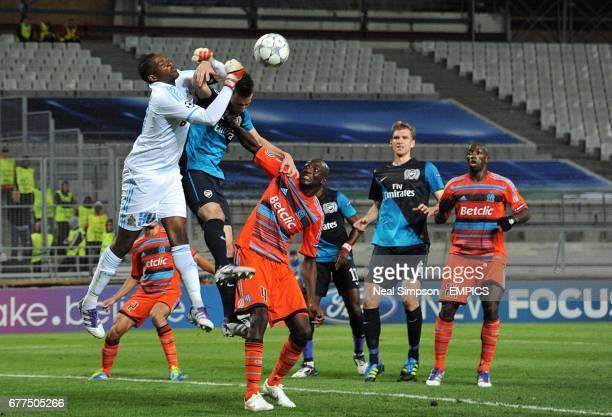 Marseille's goalkeeper Steve Mandanda punches clear under pressure from Arsenal's Laurent Koscielny