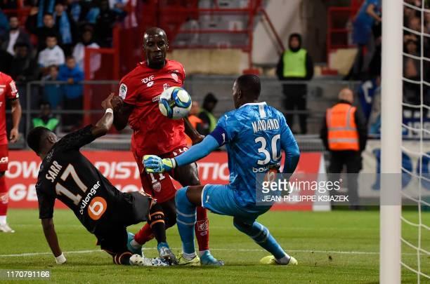 Marseille's Guinean midfielder Bouna Sarr and Marseille's French goalkeeper Steve Mandanda fights for the ball with Dijon's Cape Verdean forward...