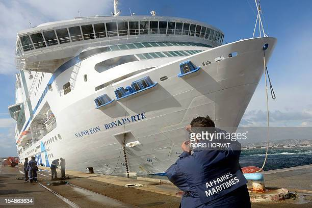 A Marseille's harbour employee takes pictures of the ferry NapoleonBonaparte of the French SNCM company which tilts to the side against a quay on...