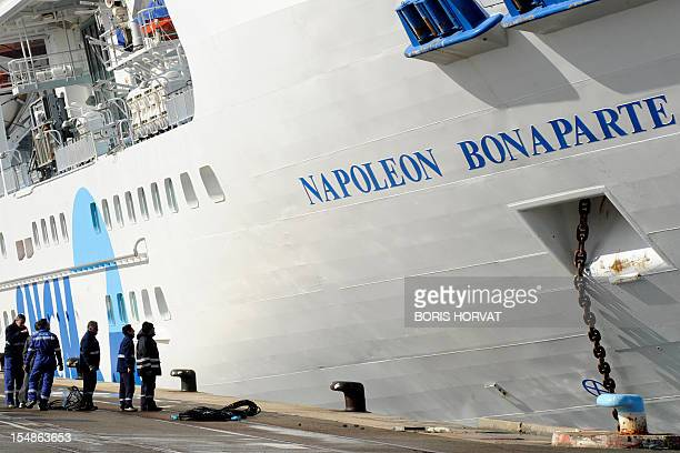 Marseille's harbour workers look at the ferry NapoleonBonaparte of the French SNCM company which tilts to the side against a quay on October 28 2012...