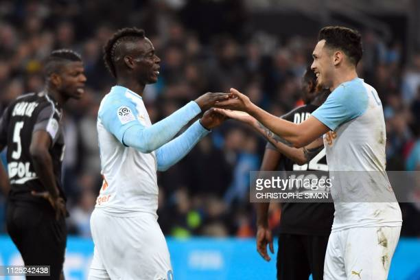 Marseille's Italian forward Mario Balotelli is congratulated by Marseille's Argentine midfielder Lucas Ocampos after scoring a goal during the French...
