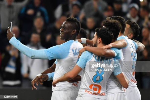 Marseille's Italian forward Mario Balotelli takes a selfie with teammates after scoring during the French L1 football match between Olympique de...