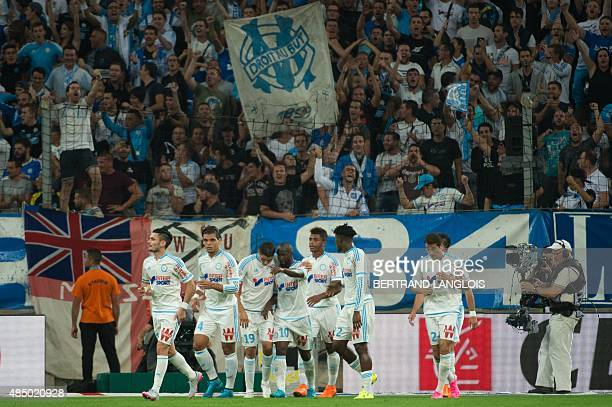 Marseille's Moroccan midfielder Abdelaziz Barrada is congratulated by teammates after scoring a goal during the French L1 football match Olympique de...