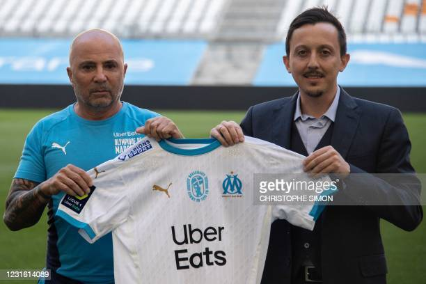Marseille's new Argentinian head coach Jorge Sampaoli poses with his team's jersey past Marseille's new Spanish president Pablo Longoria on the pitch...