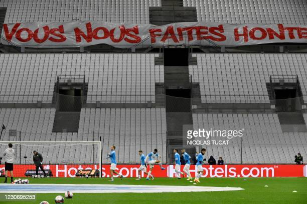 """Marseille's player warm up behind a banner setup by supporters reading """"you make me ashamed"""" prior to the French L1 football match between Olympique..."""