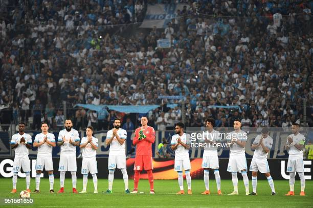 Marseille's players applaud during a tribute to late former France football coach Henri Michel who did a few days prior before to the UEFA Europa...