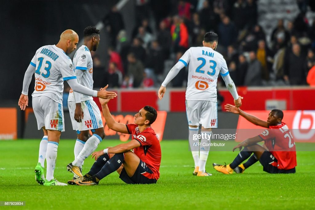 Marseille's players shake hands with Lille's players at the end of the French L1 football match between Lille OSC (LOSC) and Olympique de Marseille (OM) on October 29, 2017 at the Pierre-Mauroy Stadium in Villeneuve d'Ascq, northern France. Marseille won the match 0-1. /