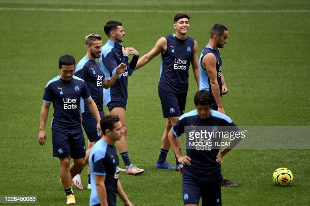 Marseille's players walk on the pitch during a training session at the Stade Velodrome in Marseille on September 11 a few days ahead of their French...