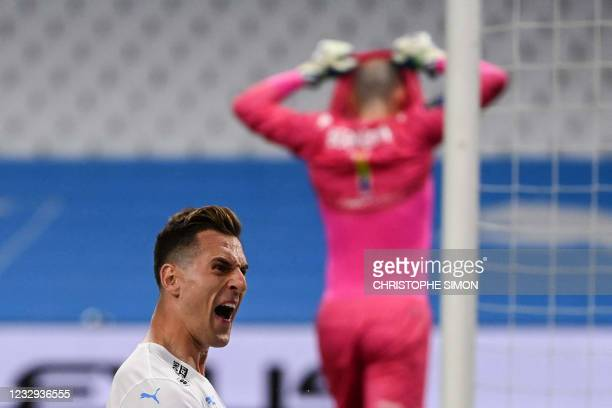 Marseille's Polish forward Arkadiusz Milik jubilates after scoring the third goals on penalty during the French L1 football match between Olympique...