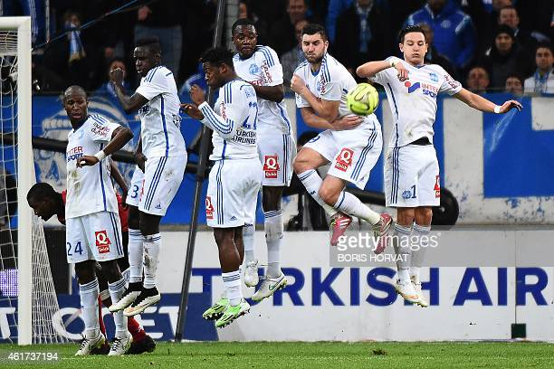 Marseille's Rod Fanni Benjamin Mendy Michy Batshuayi Giannelli Imbula AndrePierre Gignac and Florian Thauvin jump to block the ball on a free kick...