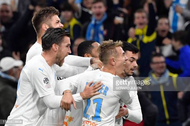 Marseille's Serbian forward Nemanja Radonjic is congratulated by his teammates after scoring a second goal during the French L1 football match...