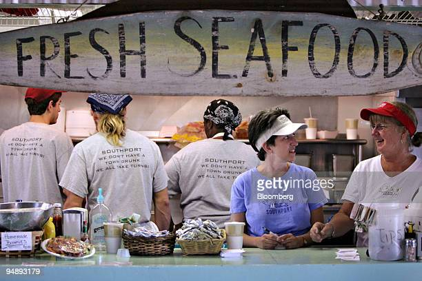 Marsha Williams, second from the left, and Dale Maher, right, work the counter at the Yacht Basin Provision Co., a seafood restaurant and bar in...