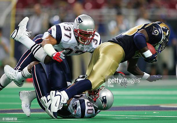 Marshal Faulk of the St. Louis Rams is brought down by Rodney Harrison and Troy Brown of the New England Patriots on November 7, 2004 at the Edward...