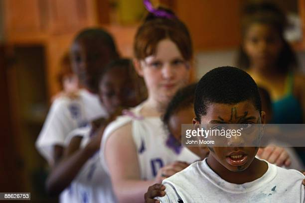 Marshal Gordon, age 8, stands with fellow homeless children while practicing a dance routine for a talent show on June 20, 2009 in Dallas, Texas. He...