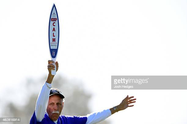 A marshal holds a sign instructing the crowd to ''keep calm'' on the fourth tee box of the north course during the first round of the Farmers...