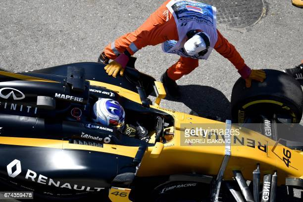 A marshal pushes the car of Renault's Russian reserve driver Sergey Sirotkin during the first practice session of the Formula One Russian Grand Prix...