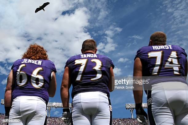 Marshal Yanda of the Baltimore Ravens and teammates stand during the national anthem as a bald eagle flys above before playing the Buffalo Bills at...