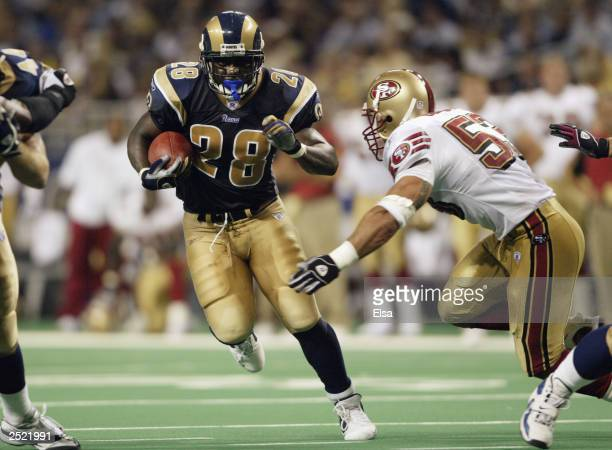 Marshall Faulk of the St Louis Rams avoids the tackle of Jeff Ulbrich of the San Francisco 49ers on September 14 2003 at the Edward Jones Dome in St...