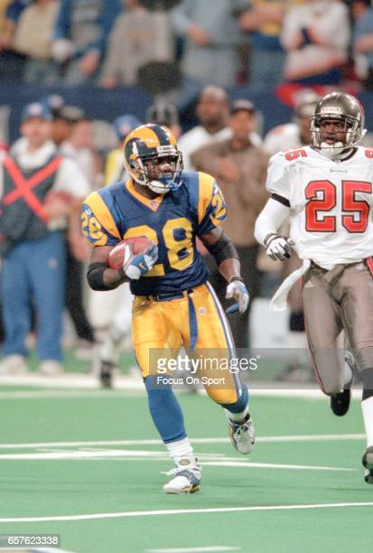 Marshall Faulk of the St Louis Rams carries the ball against the Tampa Bay Buccaneers during the NFC Conference Championship game January 23 2000 at...