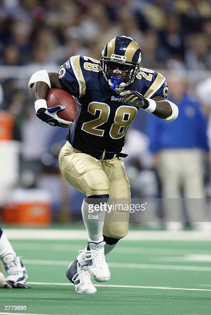 Marshall Faulk of the St Louis Rams carries the ball against the Baltimore Ravens on November 9 2003 at the Edward Jones Dome in St Louis Missouri...
